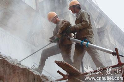 广大建设者夜以继日边安装水泥拌和场,塔吊等施工设备,边为老的大坝