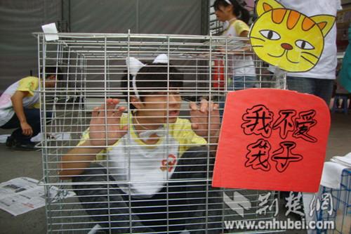 图为:大学生志愿者关笼子里扮动物