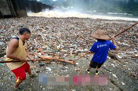 村民冒险在泄洪口捞木材